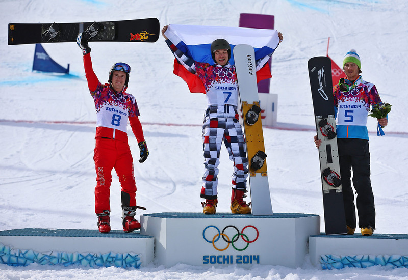 . Winner Vic Wild of Russia is flanked by second placed Nevin Galmarini (L) of Switzerland and third placed Zan Kosir (R) of Slovenia during the flower ceremony the men\'s Snowboard Parallel Giant Slalom at Rosa Khutor Extreme Park at the Sochi 2014 Olympic Games, Krasnaya Polyana, Russia, 19 February 2014.  EPA/JENS BUETTNER