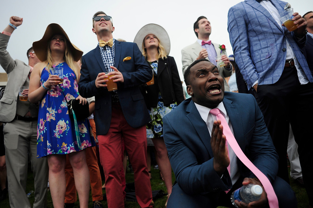 . Andy Tembon (front right) watches the race and cheers for his winning pick during the Denver Derby Party at the Performing Arts Complex in Denver, Colorado, Saturday, May 7, 2016. The event featured The Macy\'s Best Hat Contest, and also awarded 3 full ride scholarships to students heading to Colorado State University. (Brenden Neville/Special to the Denver Post)