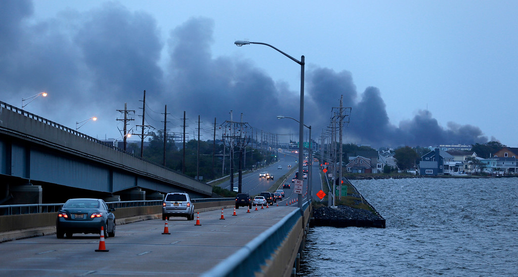 . Commuters drive on a bridge connecting the barrier island of Seaside Heights, N.J., with the mainland as cloud of smoke rises from a massive fire at the Seaside Park boardwalk, Thursday, Sept. 12, 2013, in Seaside Park, N.J. The fire, which apparently started in an ice cream shop and spread several blocks, hit the recently repaired boardwalk, which was damaged last year by Superstorm Sandy. There were no other early reports of any injuries. (AP Photo/Julio Cortez)