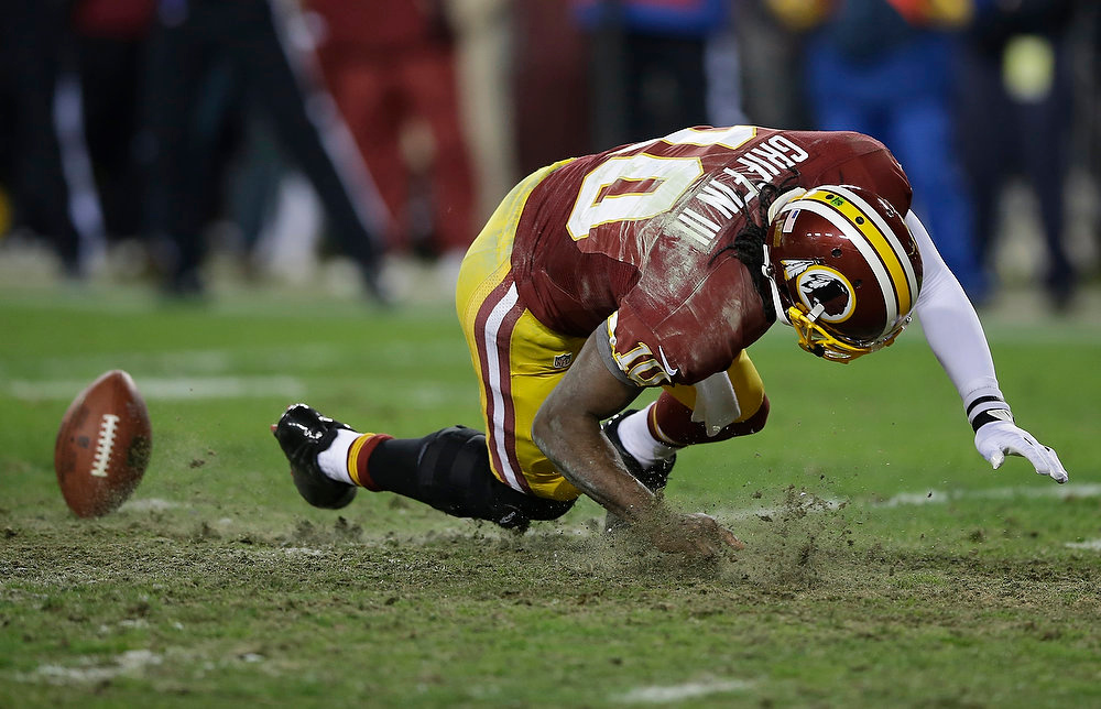 . Washington Redskins quarterback Robert Griffin III falls after twisting his knee while reaching for a loose ball during the second half of an NFL wild card playoff football game against the Seattle Seahawks in Landover, Md., Sunday, Jan. 6, 2013. (AP Photo/Matt Slocum)