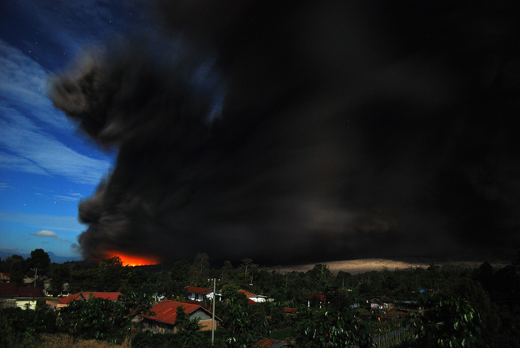 . Dark giant ash clouds rise from the crater of Mount Sinabung volcano with a scorching lava trail threatening villages during its latest eruption late October 8, 2014, seen from Karo district on Indonesia\'s Sumatra island, following an earlier eruption on October 5, 2014.  AFP PHOTO / SUTANTA ADITYA/AFP/Getty Images