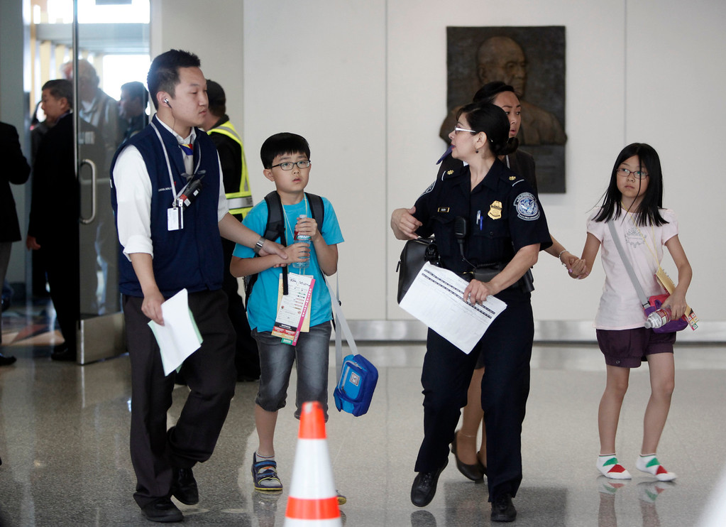 . Children are escorted from the Reflection Room at San Francisco International Airport after the crash of an Asiana Airlines Being 777 jet at San Francisco International Airport Saturday afternoon July 6, 2013.  (Karl Mondon/Bay Area News Group)