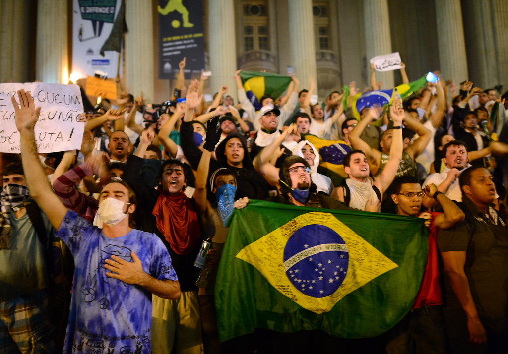 . Demonstrators shout slogans outside the Municipal theatre in downtown Rio de Janeiro on June 17, 2013, during a protest against higher public transportation fares and the use of public funds to finance international football tournaments. Protesters in several major cities are up in arms over hikes in mass transit prices -- from $1.5 to $1.6 -- as well as over the $15 billion earmarked for the two sports events amid calls for more health and education funding.   CHRISTOPHE SIMON/AFP/Getty Images