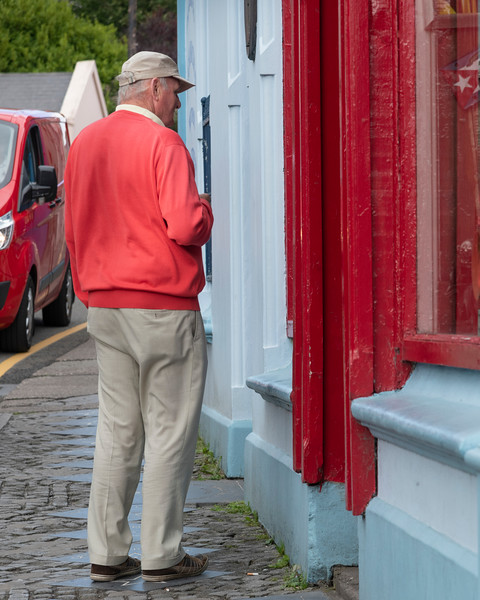 Elderly man standing outside store, Dingle, County Kerry, Republic of Ireland