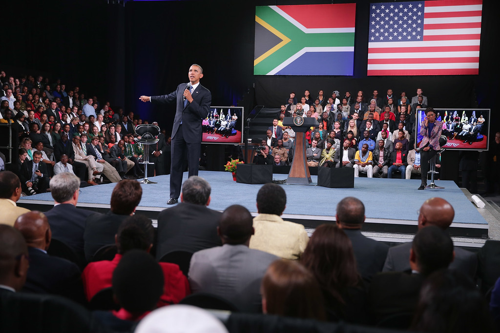 """. JOHANNESBURG, SOUTH AFRICA - JUNE 29:  U.S. President Barack Obama answers questions from the audience and from people in Nigeria, Uganda and Kenya via live video link during a \""""town hall\"""" meeting with the young African leaders at the University of Johannesburg in Soweto June 29, 2013 in Johannesburg, South Africa. South Africa is the second leg of Obama\'s three-country tour of the African continent, which includes Senegal and Tanzania.  (Photo by Chip Somodevilla/Getty Images)"""