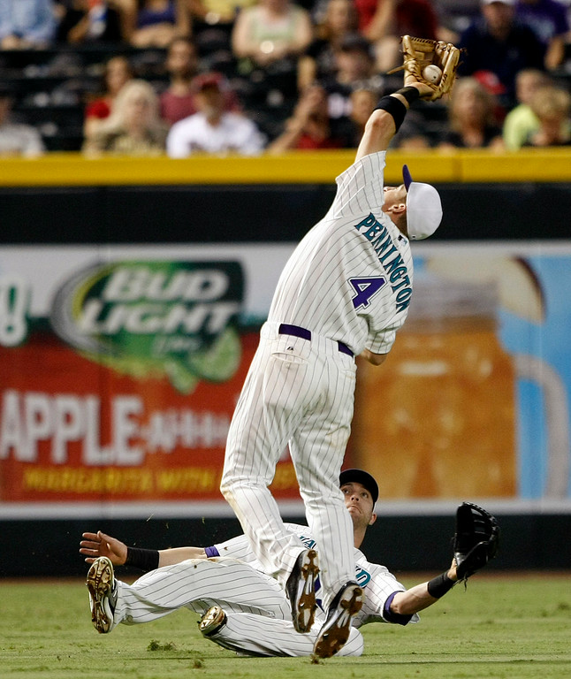 . Arizona Diamondbacks shortstop Cliff Pennington (4) makes a catch over left fielder Nolan Reimoid in the third inning during a baseball game against the Colorado Rockies, Saturday, Aug. 30, 2014, in Phoenix. (AP Photo/Rick Scuteri)