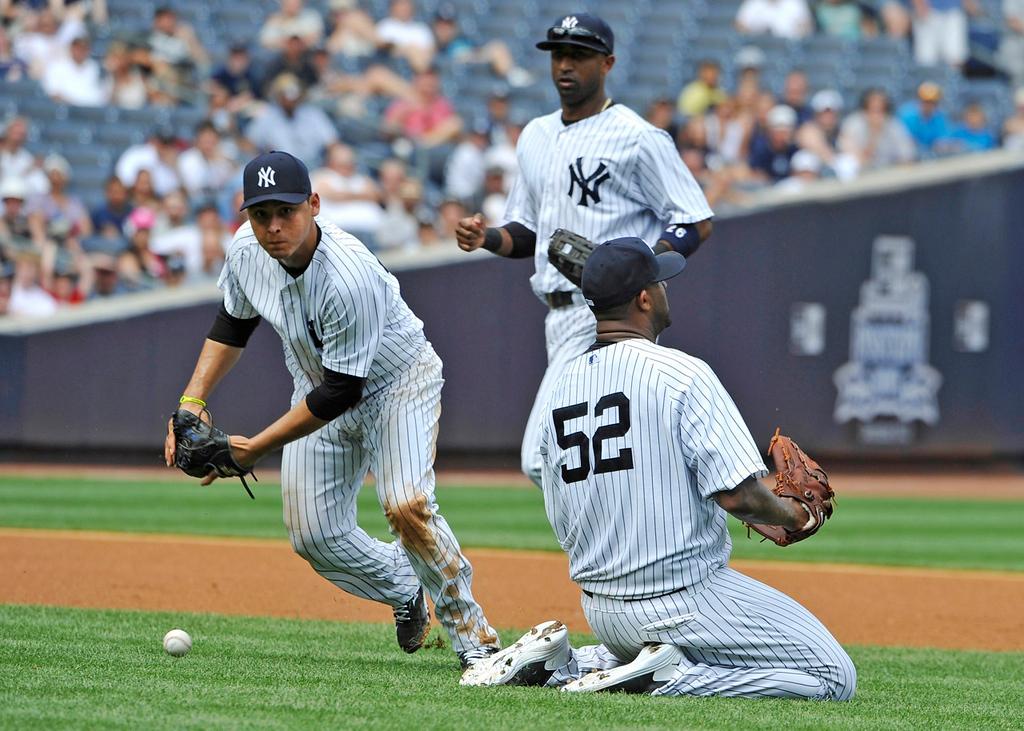 . Yankees third baseman Luis Cruz, left,  shortstop Eduardo Nunez, center, and starting pitcher C.C. Sabathia, right, can\'t field a single hit by Minnesota\'s Justin Morneau, allowing Jamey Carroll to score in the fourth inning. (AP Photo/Kathy Kmonicek)