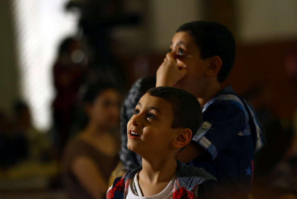 . Children celebrate Christianity\'s most joyous day, during an Easter Eve service presided over by Coptic Pope Tawadros II, at St. Mark\'s Cathedral, in Cairo, Egypt. Millions of Christians  around the world are celebrating Easter  commemorating the day when according to Christian tradition Jesus was resurrected in Jerusalem two millennia ago. (AP Photo/Ahmed Gomaa)