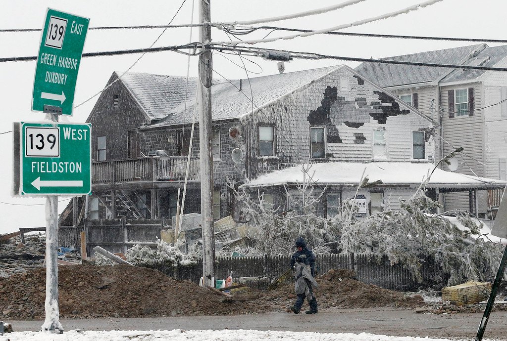 . A man removes belongings from a storm-damaged house in Marshfield, Mass., Tuesday, Jan. 27, 2015. The storm has punched out a section of the seawall in the coastal town of Marshfield, police said. (AP Photo/Michael Dwyer)