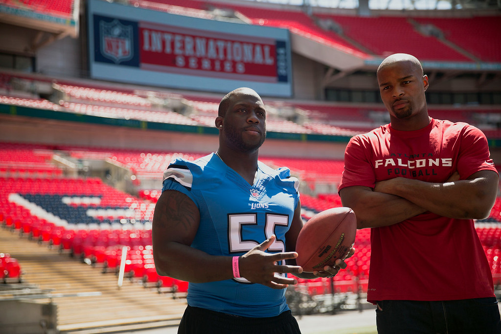 . NFL players Detroit Lions linebacker Stephen Tulloch, left, and British-born defensive end Osi Umenyiora pose for photographers at Wembley Stadium in London, Wednesday, July 16, 2014.  Six players from teams who will play in the three regular season NFL games at Wembley in the autumn were in London for media and promotional events on Wednesday.  (AP Photo/Matt Dunham)