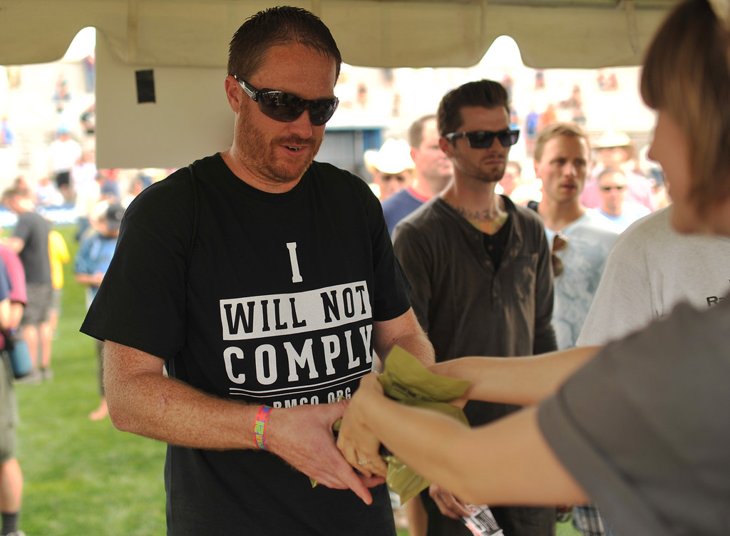 . GLENDALE, CO. - June 29: Dane Huish of Highlands Ranch is receiving the 30-round gun magazines at a farewell to arms freedom festival by Free Colorado in Infinity Park. Glendale, Colorado. June 29, 2013. Magpul Industries attended the party and handed out 1500 of their 30-round gun magazines for free.  (Photo By Hyoung Chang/The Denver Post)