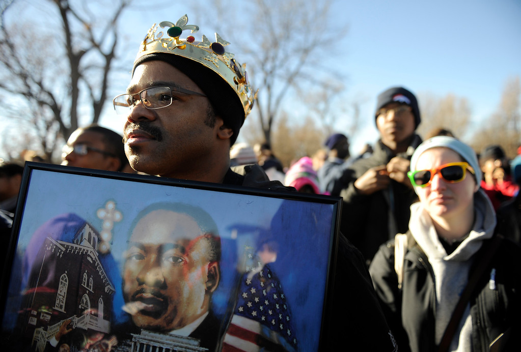 . The Martin Luther King Jr. Marade started at City Park and finished downtown. Joseph Wiggins  of Denver holds a portrait of King as he listens to speakers at the MLK statue in City Park  before the start of the march/parade on Monday, January 21, 2013.   (Photo By Cyrus McCrimmon / The Denver Post)
