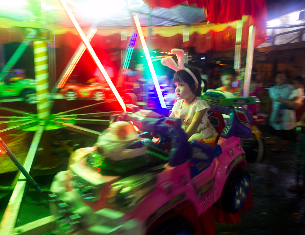 . A young girl enjoys the annual local night bazaar to mark the Thadingyut festival in downtown Yangon, Myanmar, Wednesday, Oct. 4, 2017. The Thadingyut festival, also known as lighting festival, is held around the country at the end of Buddhist Lent marking Buddha\'s descent from heaven after He sermonized the Abhidamma to His mother who was born in heaven. (AP Photo/Thein Zaw)