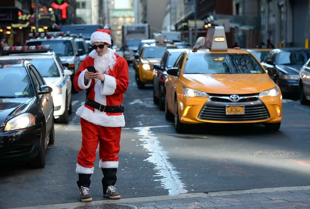 . Santa takes some photos with his cellphone in Times Square as hundreds of Santas gather for the annual Santacon festivities on December 13, 2014 in New York. AFP PHOTO/DON  EMMERT/AFP/Getty Images