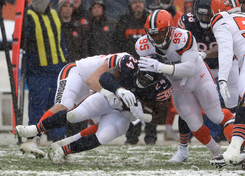 . Chicago Bears running back Jordan Howard (24) is brought down by Cleveland Browns defensive end Carl Nassib (94) and Myles Garrett (95) in the first half of an NFL football game in Chicago, Sunday, Dec. 24, 2017. (AP Photo/Nam Y. Huh)