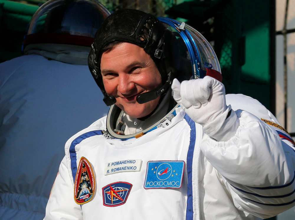 Description of . International Space Station crew member Russian cosmonaut Roman Romanenko waves as he boards the Soyuz TMA-07M spacecraft at the Baikonur cosmodrome December 19, 2012.  REUTERS/Dmitry Lovetsky/Pool