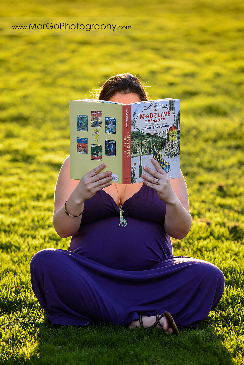 pregnant woman in long violet dress sitting on the green grass and reading children book at Lick Mill Park in Santa Clara