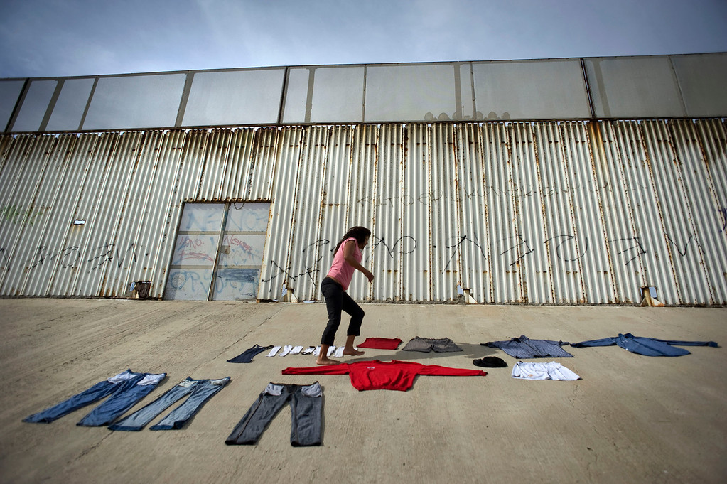 . Marta Sandoval, 36, lays out clothing to dry on the bank of the Tijuana River canal, which has become home to hundreds of people deported from the US, in Tijuana, Mexico, 03 May 2013. In the background is the US-Mexico border wall. Sandoval, was deported from the US and has been living in the river canal. Heightened US border security and record numbers of deportations from the US have created a growing population of people who live homeless in Mexican cities that border with the United States. Many had lived for years undocumented in the US and have little or no family and other support in Mexico, and are subject to fall into depression, substance abuse and crime. Tijuana, Mexico, borders on the US city of San Diego, California.  EPA/DAVID MAUNG