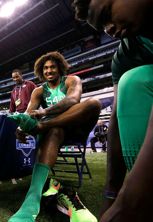 . USC defensive lineman Leonard Williams puts his socks on at the NFL football scouting combine in Indianapolis, Sunday, Feb. 22, 2015. (AP Photo/David J. Phillip)