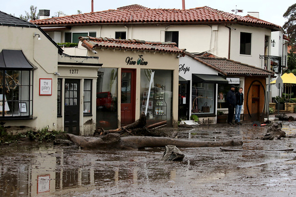 . Debris and mud cover the street in front of local area shops after heavy rain brought flash flooding on Tuesday, Jan. 9, 2018 in Montecito, Calif. At least five people were killed and homes were swept from their foundations Tuesday as heavy rain sent mud and boulders sliding down hills stripped of vegetation by a gigantic wildfire that raged in Southern California last month. (Daniel Dreifuss)