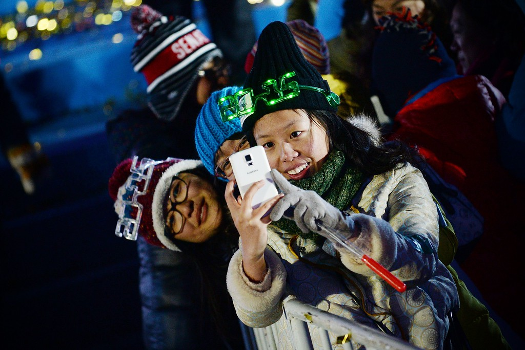 . A group of women take a photo to celebrate new year during a New Year\'s Eve countdown event in front of Beijing\'s National Stadium, Known as the Bird\'s Nest in Beijing on January 1, 2015. Beijing is bidding to host the 2022 Winter Olympic Games, with a decision on the winning city to be made in July 2015.        AFP PHOTO / WANG ZHAOWANG ZHAO/AFP/Getty Images