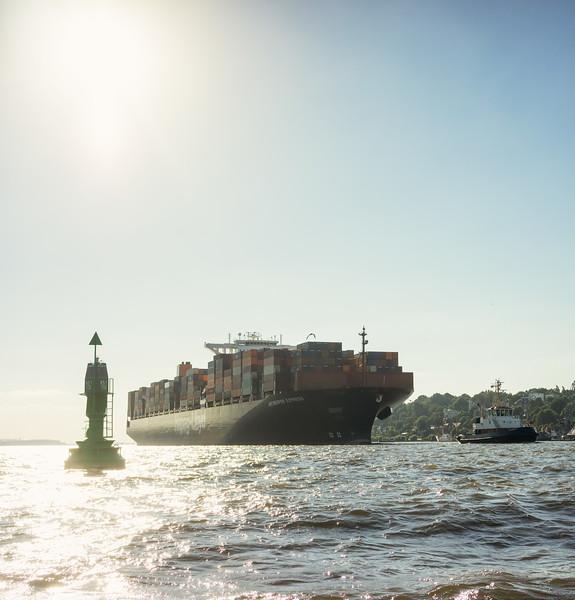 Containerschiff auf der Elbe bei Gegenlicht mit Schlepper bugsier 7