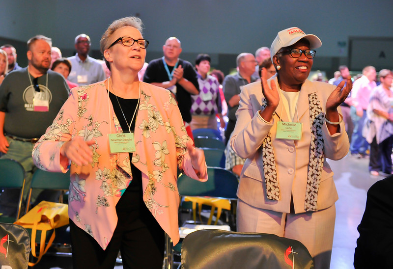 Chris Newman-Jacobs (left), and Michelle Cobb clap to music at the Friday Plenary at the 2017 INUMC Annual Conference in Indianapolis.