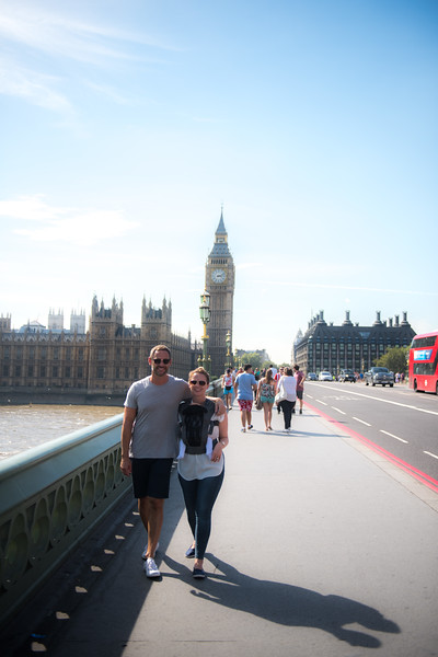 Izmi_Baby_Carrier_Breeze_Mid_Grey_Lifestyle_Front_Facing_Carry_Mum_And_Dad_Walking_In_City_Big_Ben_Wide_Angle.jpg