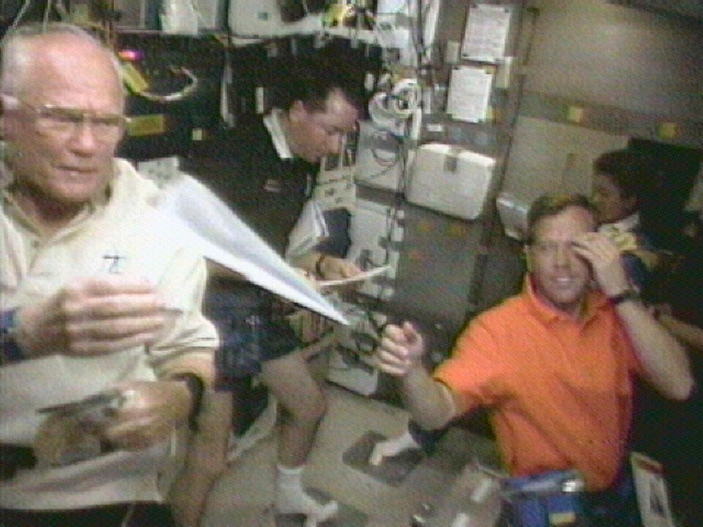 . Astronaut John Glenn, far left, retrieves a paper airplane for pilot Steven Lindsey, front right, in this televised view from Discovery\'s middeck Sunday, Nov. 1, 1998.  Astronaut Stephen Robinson, left, and Japanese astronaut Chiaki Mukai look over paper work in the background. (AP Photo/NASA TV)
