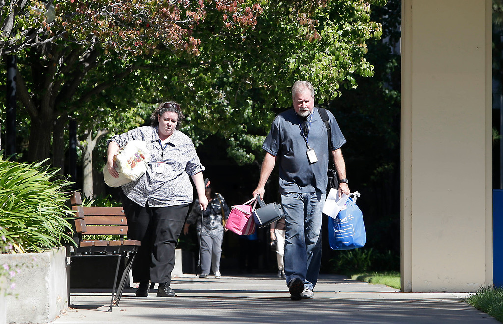 . Furloughed federal employees leave the federal offices in Sacramento, Calif., Tuesday, Oct. 1, 2013.  The impact of the partial federal government  shutdown began to take effect as employees leave their federal jobs.(AP Photo/Rich Pedroncelli)