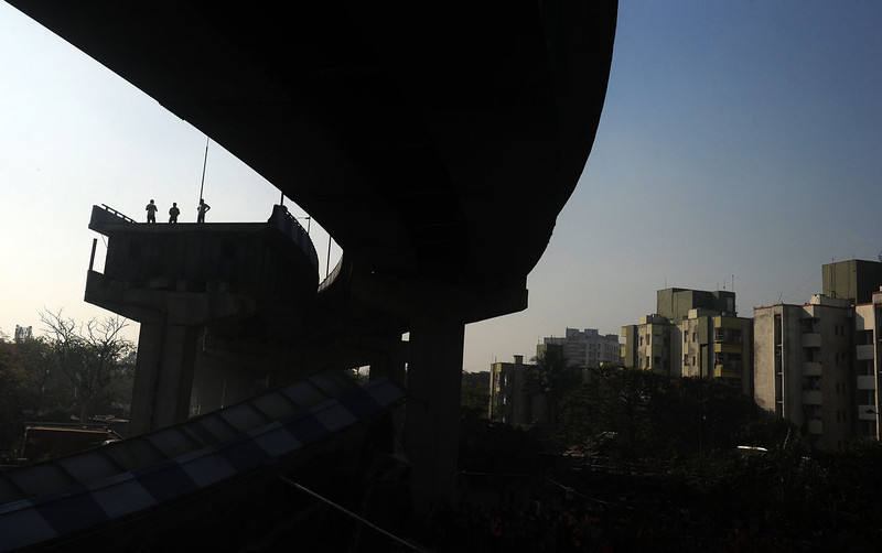 . Indian onlookers stand near the collapsed portion of the flyover in Kolkata on March 3, 2013. A huge portion of a flyover on the eastern side of the Indian metropolis collapsed leaving three persons injured, the flyover connects the airport with Eastern Metropolitan Bypass and the eastern and southern suburbs.   As the debris fell into a canal running below the flyover, it took down a truck the driver and two others were rescued from the canal by fire-brigade personnel and locals.   DIBYANGSHU SARKAR/AFP/Getty Images