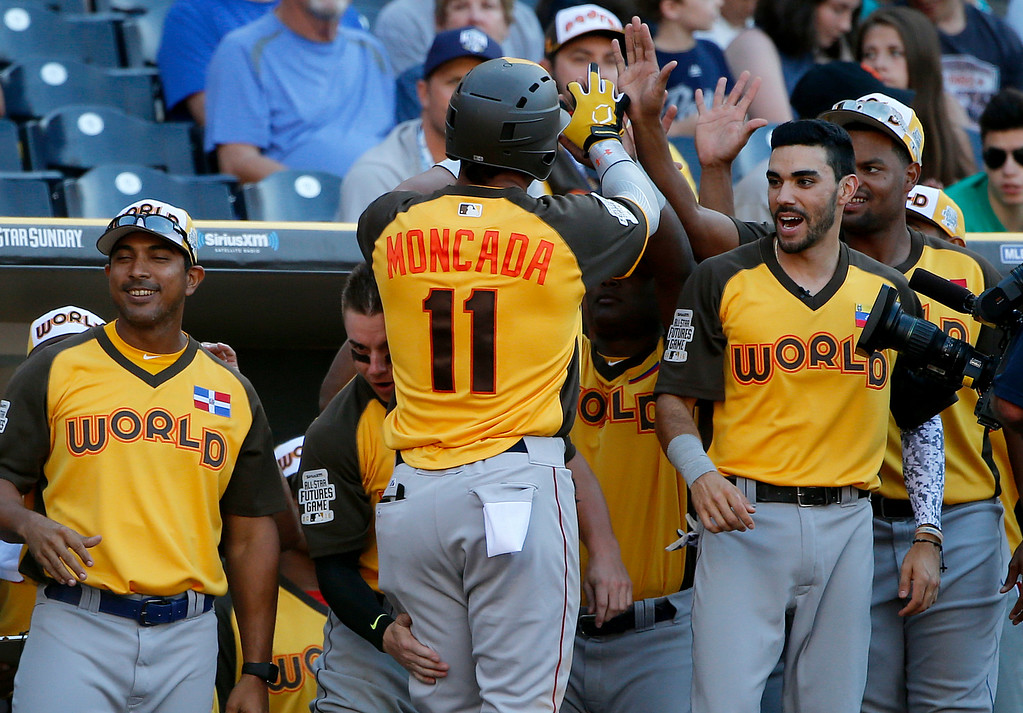 . World Team\'s Yoan Moncada, of the Boston Red Sox, greets teammates after hitting a two-run home run against the U.S. Team during the eighth inning of the All-Star Futures baseball game, Sunday, July 10, 2016, in San Diego. (AP Photo/Lenny Ignelzi)