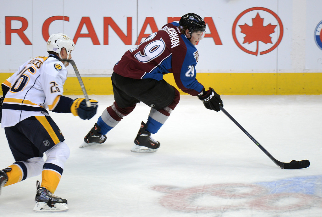 . DENVER, CO - OCTOBER 04 : Nathan MacKinnon of Colorado Avalanche (29) controls the puck against  Matt Hendricks of Nashville Predators (26) in the 2nd period of the game at Pepsi Center. Denver, Colorado. October 4, 2013. (Photo by Hyoung Chang/The Denver Post)