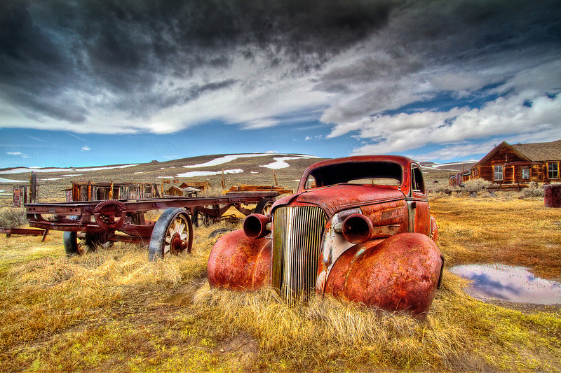 """Rusted car in a state of arrested decay.  Yes, that is what they call Bodie, California today-arrested decay. In its heyday in the 1880's, Bodie was a thriving gold mining town. Located 8,000 feet above sea level in the rugged Eastern Sierras , Bodie was , to quote one of its citizens """"the worst climate out of doors"""". But the worst climate wasn't just the weather. With a peak number of 10,000 people, it had 65 saloons giving ample opportunity for robberies, hold ups, street fights and killings with monotonous regularity. One little girl, whose family was taking her to this remote and infamous town wrote in her diary: """" Goodbye God, I am going to Bodie.""""  After the gold was gone and two fires devastated the town, it was abandoned for good in 1920 with only 5%  of the buildings remaining. In 1962, the iconic ghost town was designated a state historic park. It is now maintained as the park service calls it """" in a state of arrested decay"""" leaving Bodie to its own fate as time and the elements slowly wear it down. This is my photograph showing a rusting car among other worn man-made equipment during a cold, rainy and dreary day- a classic Bodie afternoon"""