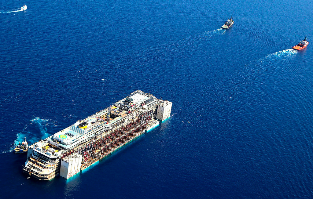 . In this aerial picture provided by the Italian Civil Protection Department, the wreck of the Costa Concordia is towed by two tugboats as it leaves behind the tiny Tuscan island of Isola del Giglio,  Italy, Wednesday, July 23, 2014. The Costa Concordia cruise liner has begun its final voyage away from the tiny Italian island where it capsized on Jan. 13, 2012, killing 32 people. (AP Photo/Courtesy of the Italian Civil Protection Department)