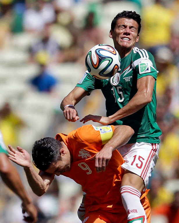 . Mexico\'s Hector Moreno, top, gets above Netherlands\' Robin van Persie during the World Cup round of 16 soccer match between the Netherlands and Mexico at the Arena Castelao in Fortaleza, Brazil, Sunday, June 29, 2014. (AP Photo/Natacha Pisarenko)