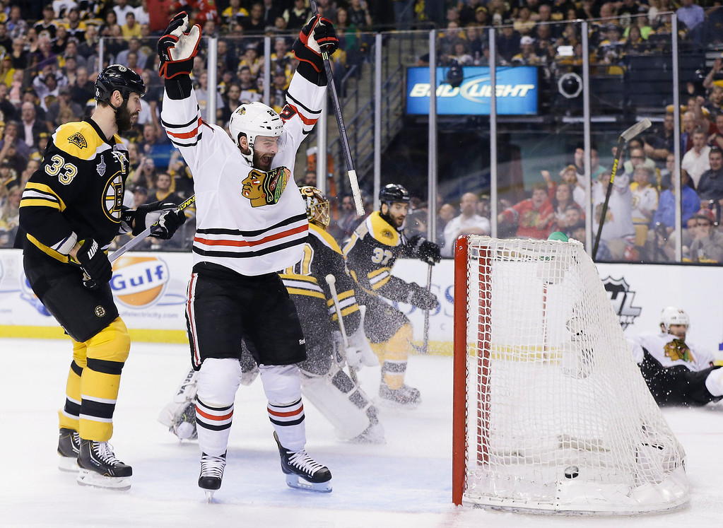 . Chicago Blackhawks left wing Brandon Saad, center, celebrates a goal by Chicago Blackhawks center Michal Handzus, right, of Slovakia, in front of Boston Bruins defenseman Zdeno Chara (33), of Slovakia, during the first period in Game 4 of the NHL hockey Stanley Cup Finals, Wednesday, June 19, 2013, in Boston. (AP Photo/Elise Amendola)