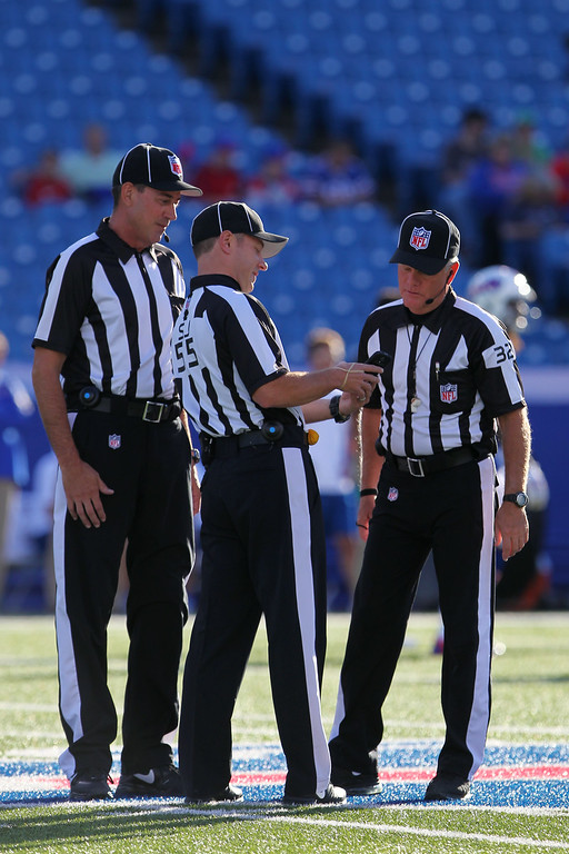 . Officials look at a smart phone during the first half of a preseason NFL football game between the Detroit Lions and the Buffalo Bills, Thursday, Aug. 28, 2014, in Orchard Park, N.Y. (AP Photo/Bill Wippert)