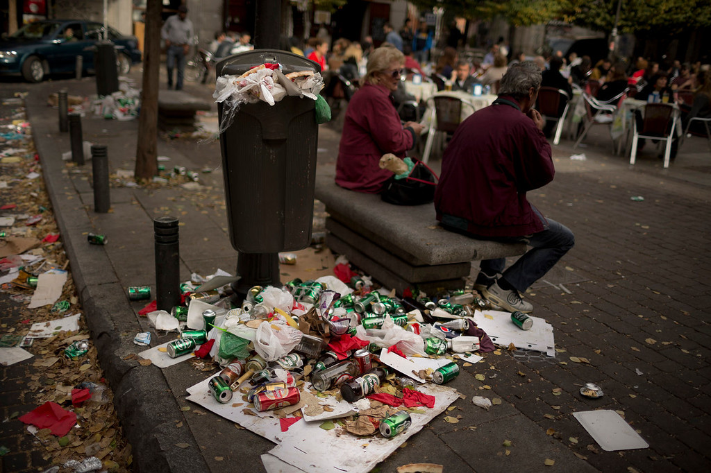 . A couple sit on a public bench as garbage spills out of a full trash can during the sixth day of a garbage collectors strike, in Madrid, Sunday, Nov. 10, 2013. Street cleaners and garbage collectors who work in the city\'s public parks walked off the job in a strike called by trade unions to contest the planned layoff of more than 1,000 workers. Madrid\'s municipal cleaning companies, which have service supply contracts with the city authorities, employ some 6,000 staff. (AP Photo/Daniel Ochoa de Olza)