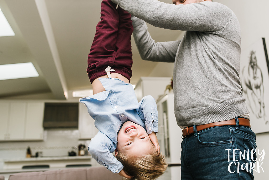 Boy being swung by his feet by dad.  Lifestyle in-home family photoshoot in Marin, CA by Tenley Clark Photography.