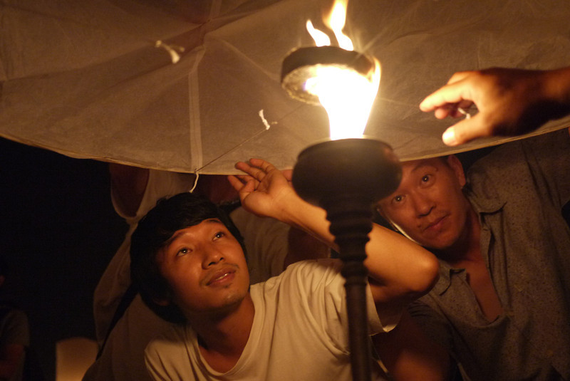 Lee inspects the lantern as it fills with hot air during Loy Krathong in Chiang Mai, Thailand