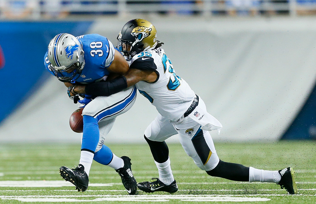 . Jacksonville Jaguars cornerback Demetrius McCray (35) forces a Detroit Lions running back George Winn (38) fumble in the second half of a preseason NFL football game at Ford Field in Detroit, Friday, Aug. 22, 2014. (AP Photo/Rick Osentoski)