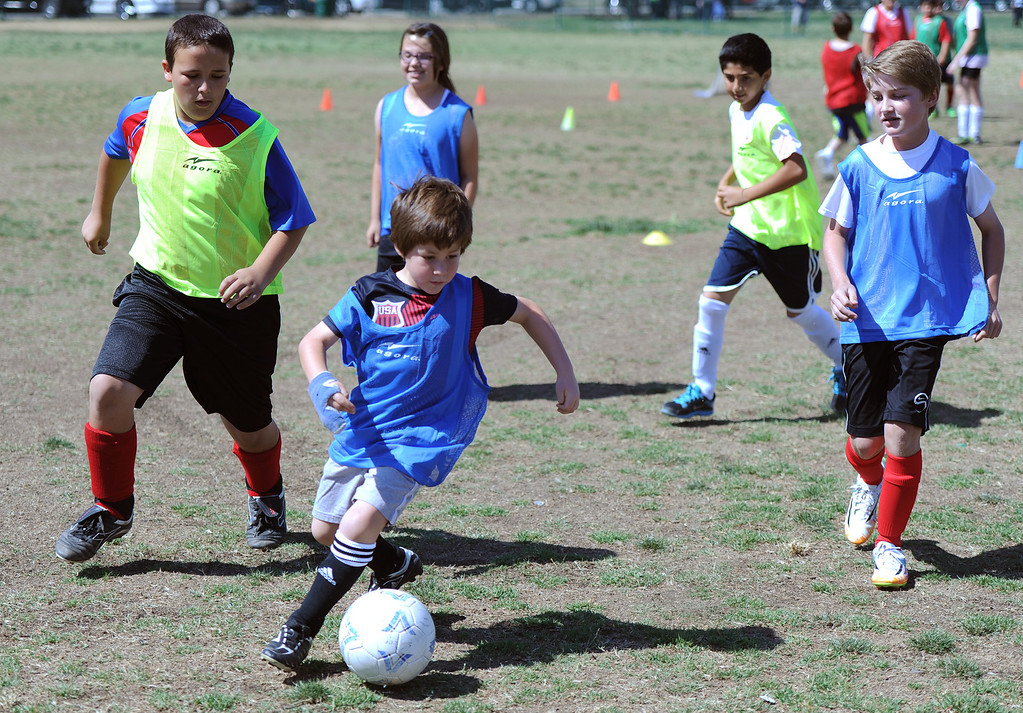 """. Shane Gorokhousky (center) takes control of the ball while chased by (l-) Jacob Eskelin, Caitlyn Burnett, Dariush Dahesh and Evan Pritchard. In honor of the AYSO\'s 50th anniversary as the nation�s most active and open youth soccer organization, kids at Balboa Park in Encino will join efforts around the country Saturday--over 500,000 players,125,000 volunteers,100 community-based events and a national soccer festival--to set a world record for the \""""largest pickup game on Earth.\"""" Encino, CA. 5/3/2014(Photo by John McCoy / Los Angeles Daily News)"""