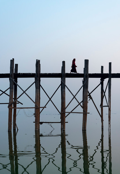 Buddhist monk crosses the U Bein Bridge - the longest teakwood footbridge in the world in Amarapura near Mandalay, Burma (Myanmar)