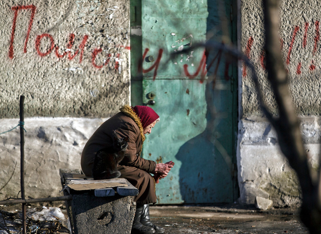 """. In this Monday, Feb. 23, 2015 photo, an elderly woman and a cat sit on a bench outside a damaged apartment building in Debaltseve, Ukraine. Ukraine delayed a promised pullback of heavy weapons from the front line Monday, blaming continuing attacks from separatist rebels in eastern Ukraine. Writing on the wall reads \""""Help Me !\"""" (AP Photo/Vadim Ghirda)"""