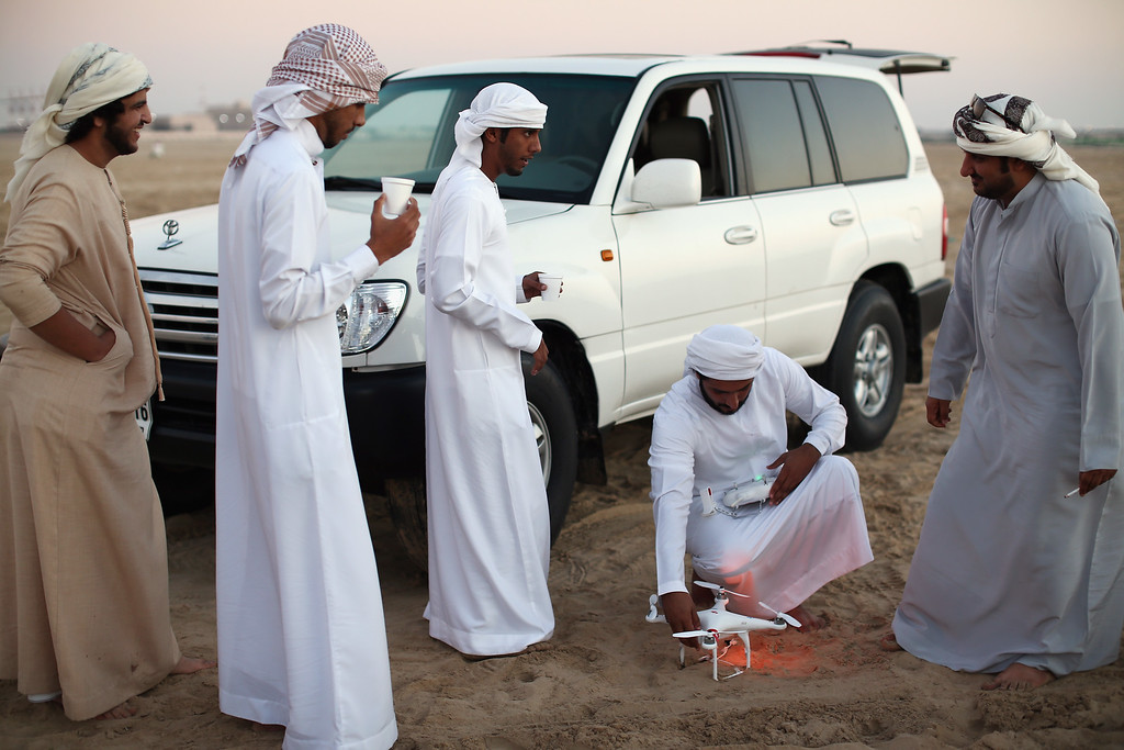 . Emirati men prepare to use a small helicopter drone to take lure up before letting their Falcons catch it on February 3, 2015 in Abu Dhabi, United Arab Emirates. T(Photo by Dan Kitwood/Getty Images)