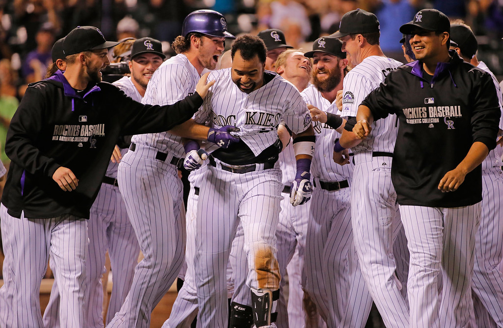 . DENVER, CO - SEPTEMBER 18:  Wilin Rosario #20 of the Colorado Rockies is mobbed by his teammates after hitting the game winning walk off two run home run off of Addison Reed #43 of the Arizona Diamondbacks at Coors Field on September 18, 2014 in Denver, Colorado. The Rockies defeated the Diamondbacks 7-6.  (Photo by Doug Pensinger/Getty Images)