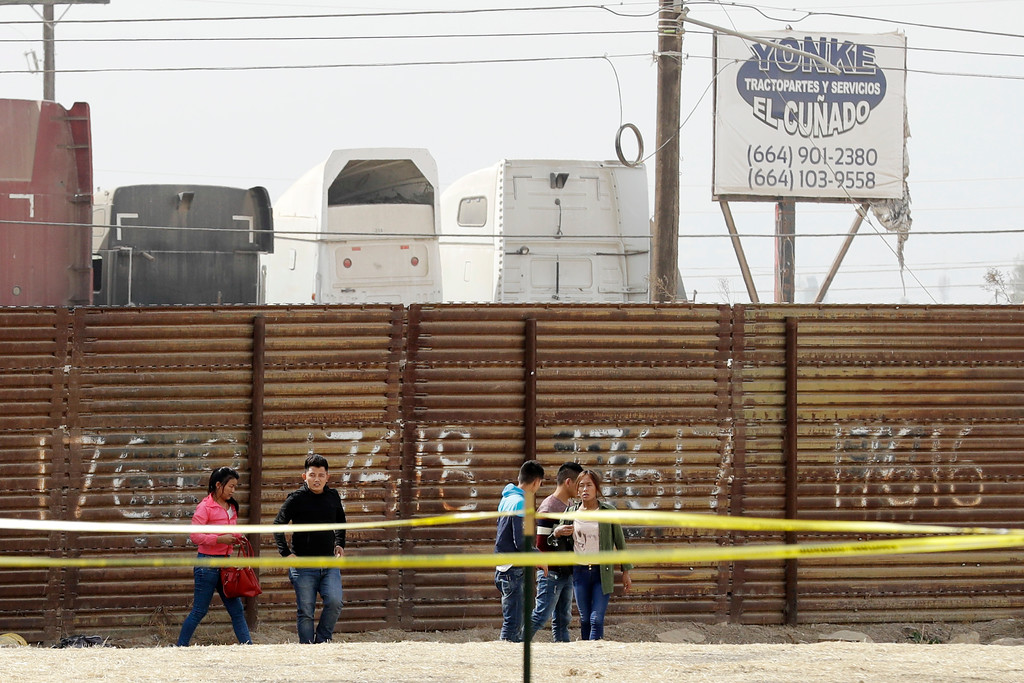 . A group of people walk towards Border Patrol agents on horseback after being spotted crossing crossing the border illegally from Tijuana, Mexico, behind, near where prototypes for a border wall are being constructed Thursday, Oct. 19, 2017, in San Diego. Companies are nearing an Oct. 26 deadline to finish building eight prototypes of President Donald Trump\'s proposed border wall with Mexico. (AP Photo/Gregory Bull)