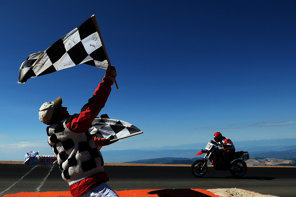 . Finish line flag man Brian Oliver welcomes Pikes Peak 450 racer George Lloyd to the summit during the 91st running of the Pikes Peak International Hill Climb Sunday, June 30, 2013. (Michael Ciaglo, The Gazette)