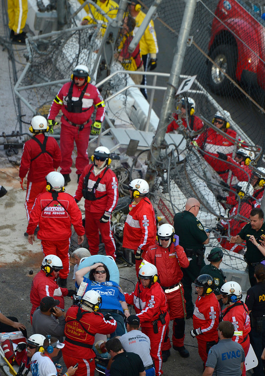 . Emergency officials transport a fan who was hit by debris after Kyle Larson\'s car slammed into the wall and safety fence along the front grandstands on the final lap of the NASCAR Nationwide Series auto race at Daytona International Speedway in Daytona Beach, Fla., Saturday, Feb. 23, 2013.(AP Photo/Phelan M. Ebenhack)